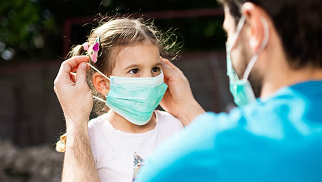 A man wearing a disposable protective face mask is shown helping a young girl put on her own mask.