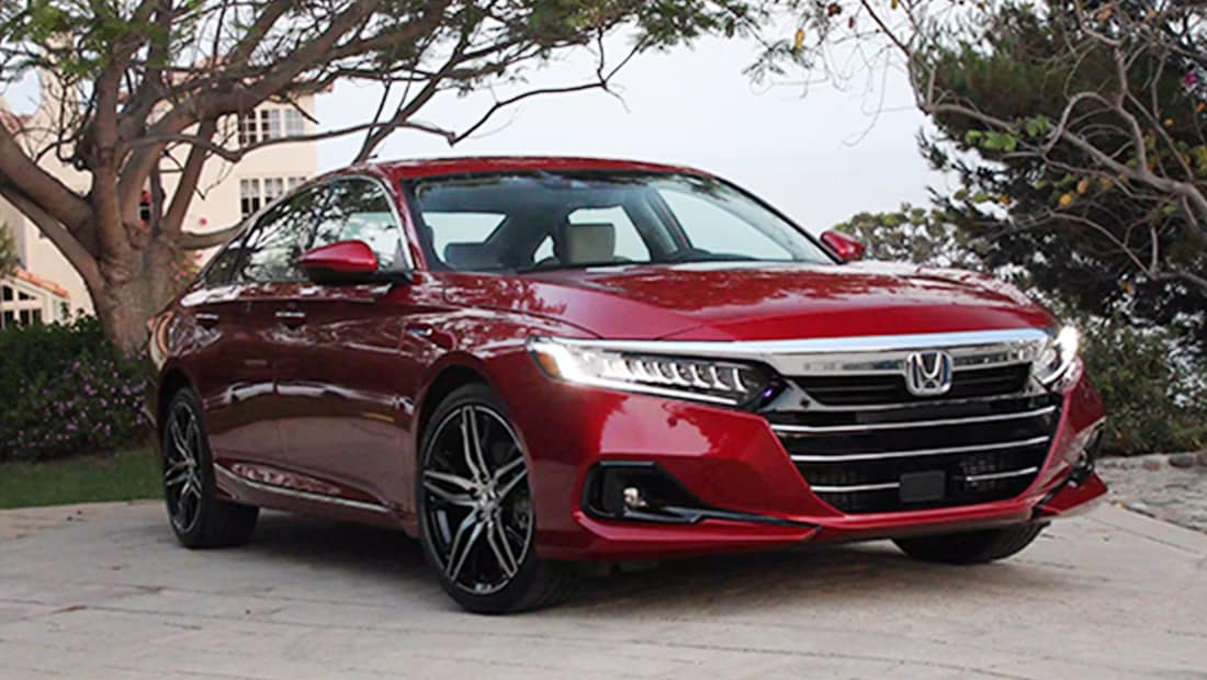 Front passenger-side view of the 2021 Honda Accord Hybrid in Radiant Red Metallic parked on a tree-lined driveway.