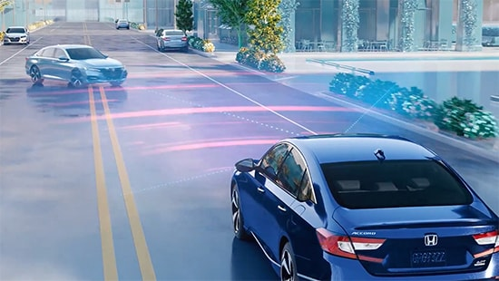 3/4 rear driver's view of the 2018 Honda Accord Touring 2.0T in Obsidian Blue Pearl demonstrating the Honda Sensing® with Collision Mitigation Braking System™ with a 2019 Honda Accord Touring 2.0T in Lunar Silver Metallic crossing lanes.