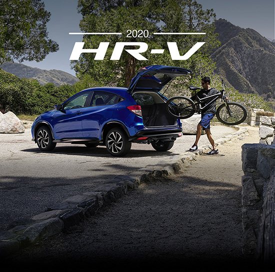 Rear three-quarter driver-side view of the 2020 HR-V AWD Sport in Aegean Blue Metallic parked at a scenic overlook with the tailgate open and a bicycle being loaded into the rear.
