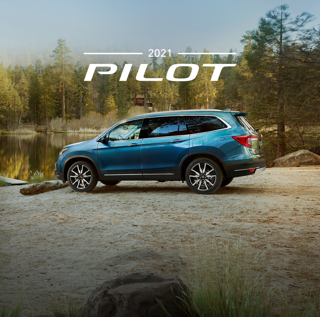 Driver-side profile of the 2019 Pilot Elite parked next to a lake in a forest environment.