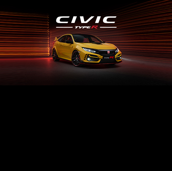 Front three-quarter passenger-side view of the 2021 Honda Civic Type R Limited Edition shown in Phoenix Yellow, parked in a dramatically lit studio environment.