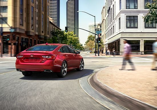 3/4 rear passenger's view of the 2019 Honda Accord Touring 2.0T in Radiant Red Metallic turning around an urban street.