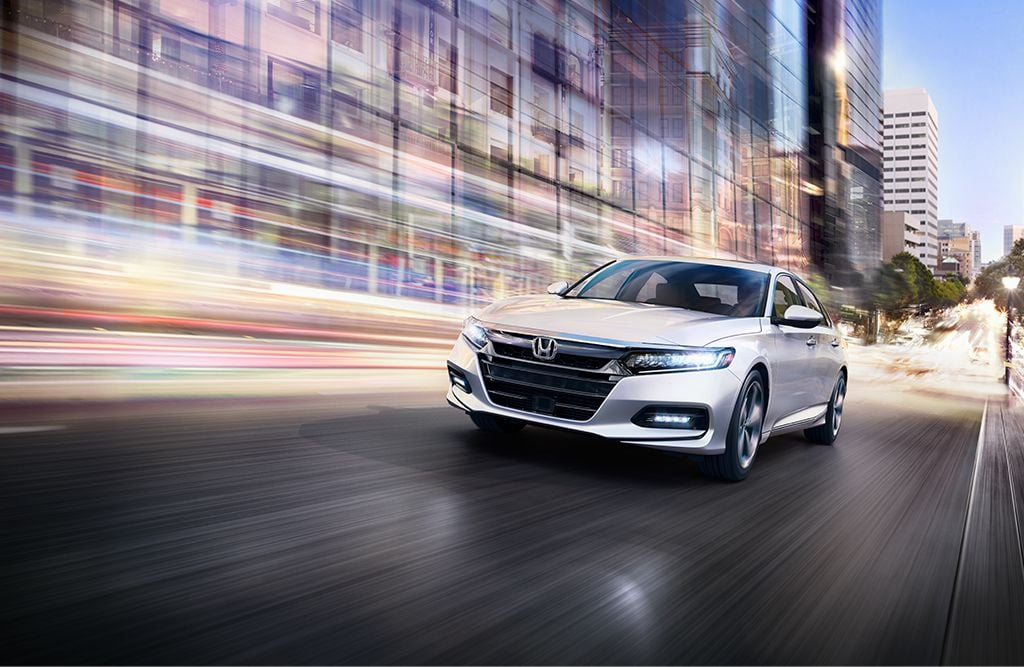 7/8 front driver's view of the 2019 Honda Accord Touring 2.0T in Platinum White Pearl speeding down a city street in the evening.