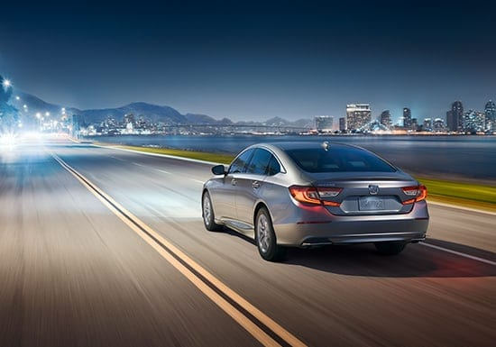 Rear 3/4 of 2019 Honda Accord LX driving at night with the auto high-beam headlights feature.