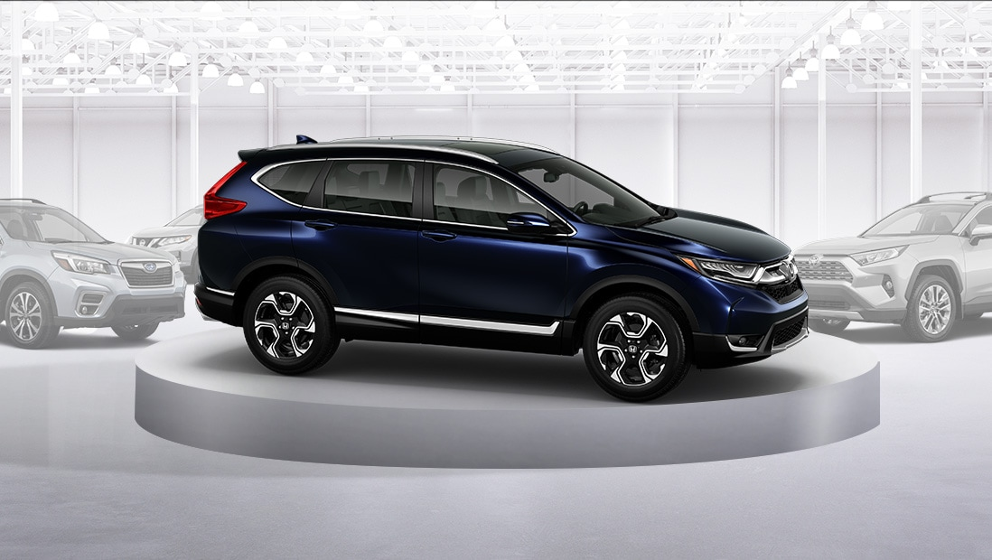 Front 7/8 passenger's side view of the 2019 Honda CR-V in Obsidian Blue Pearl parked in front of competitor SUVs in showroom environment