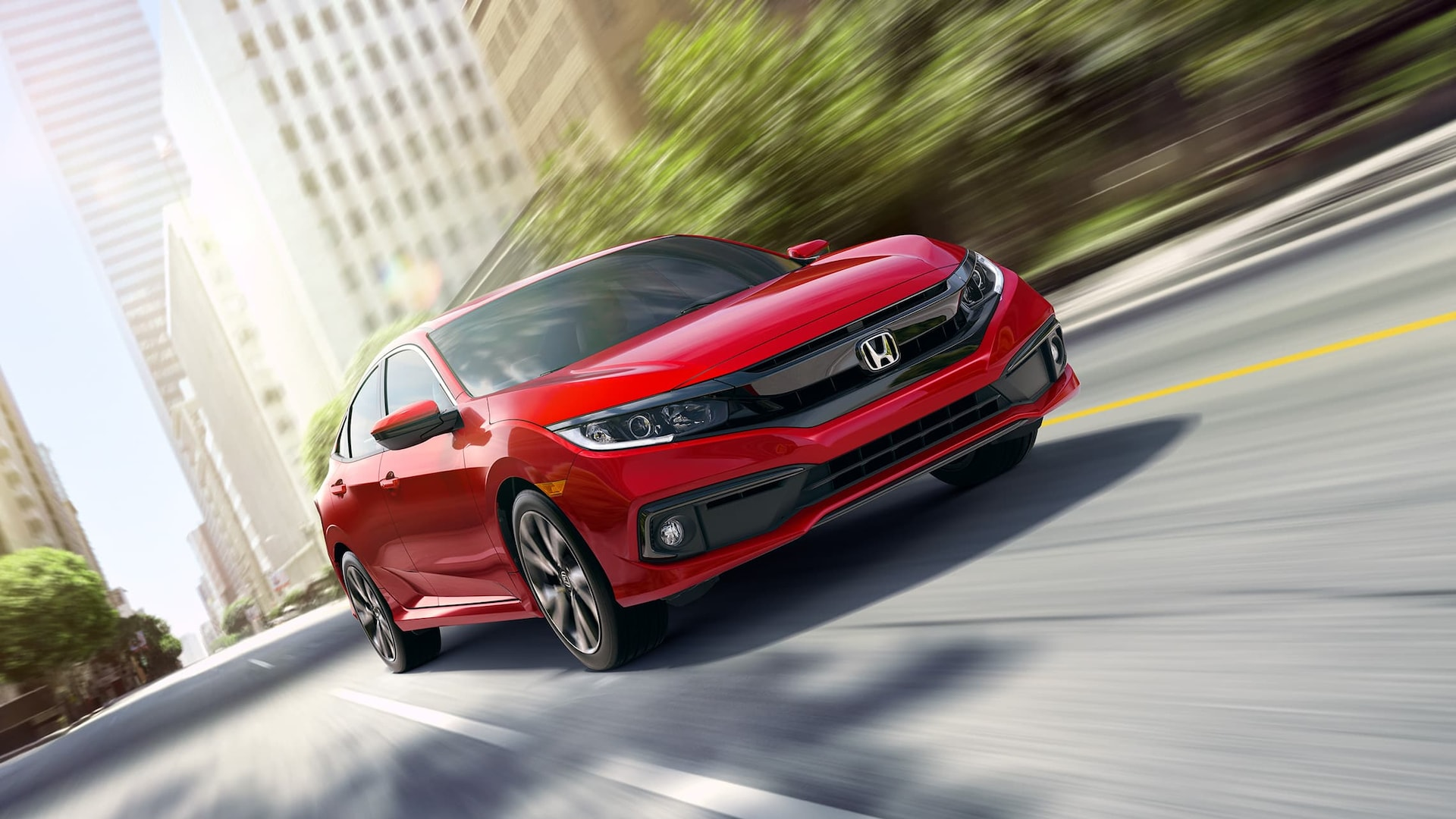 Front 3/4 passenger's side view of 2019 Honda Civic Sport Sedan in Rallye Red driving through city environment.