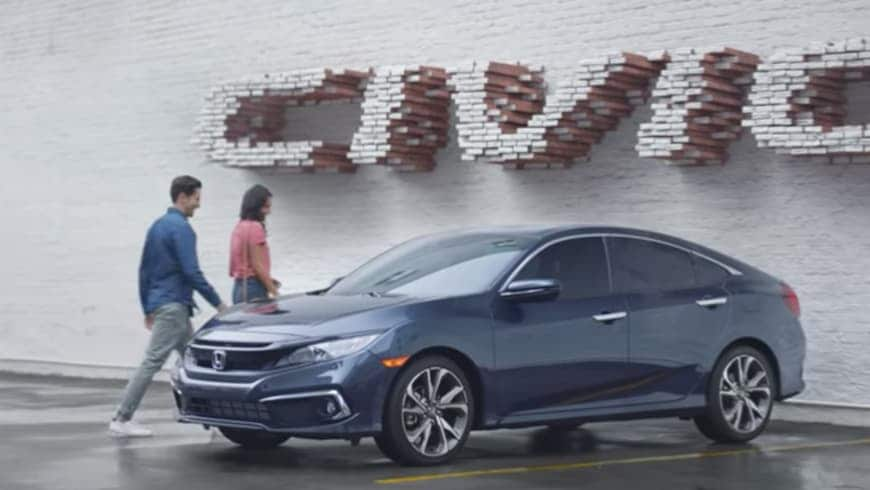 Front 3/4 driver's side view of 2020 Honda Civic Touring Sedan in Cosmic Blue Metallic parked outside dealership.