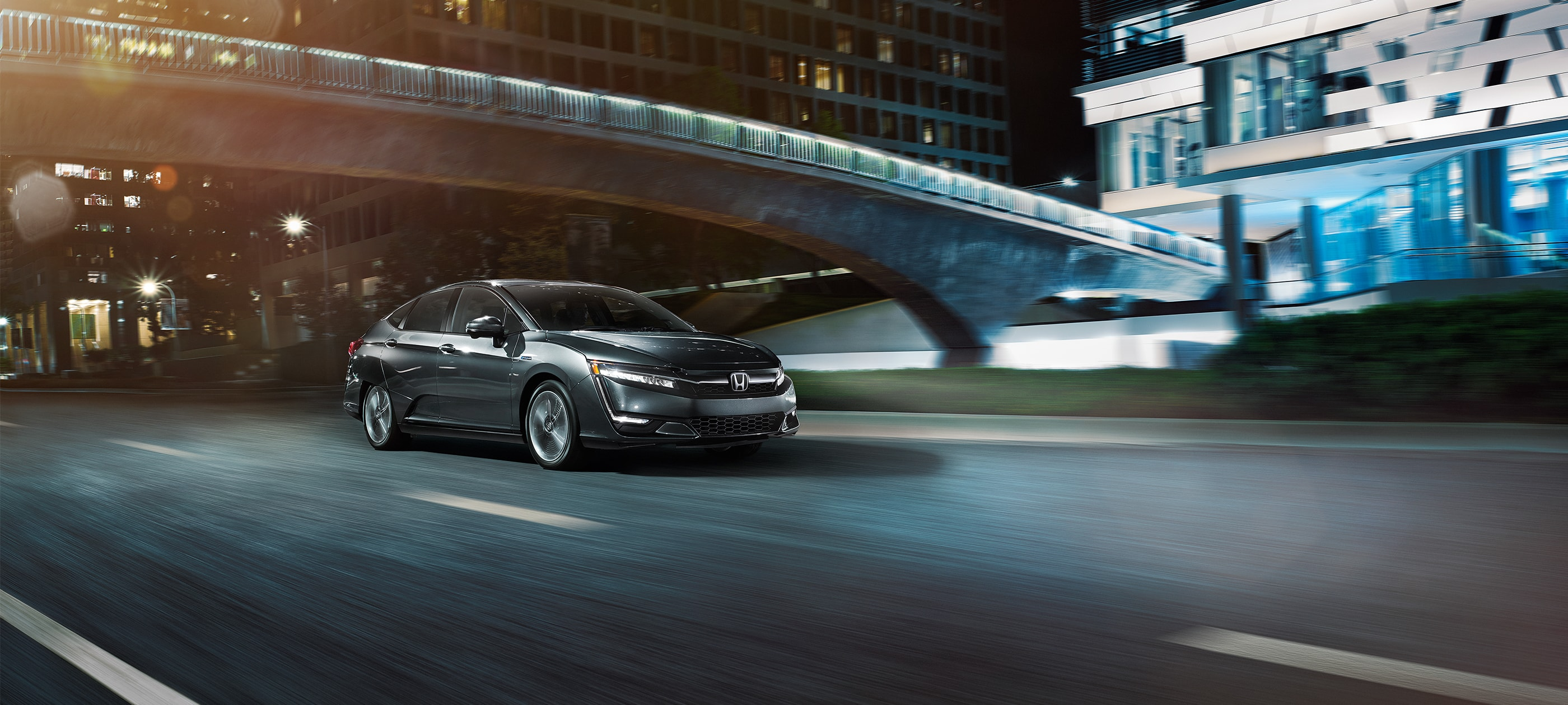 Front ¾ passenger-side view of 2019 Honda Clarity PHEV in Modern Steel Metallic driving on city road at night.