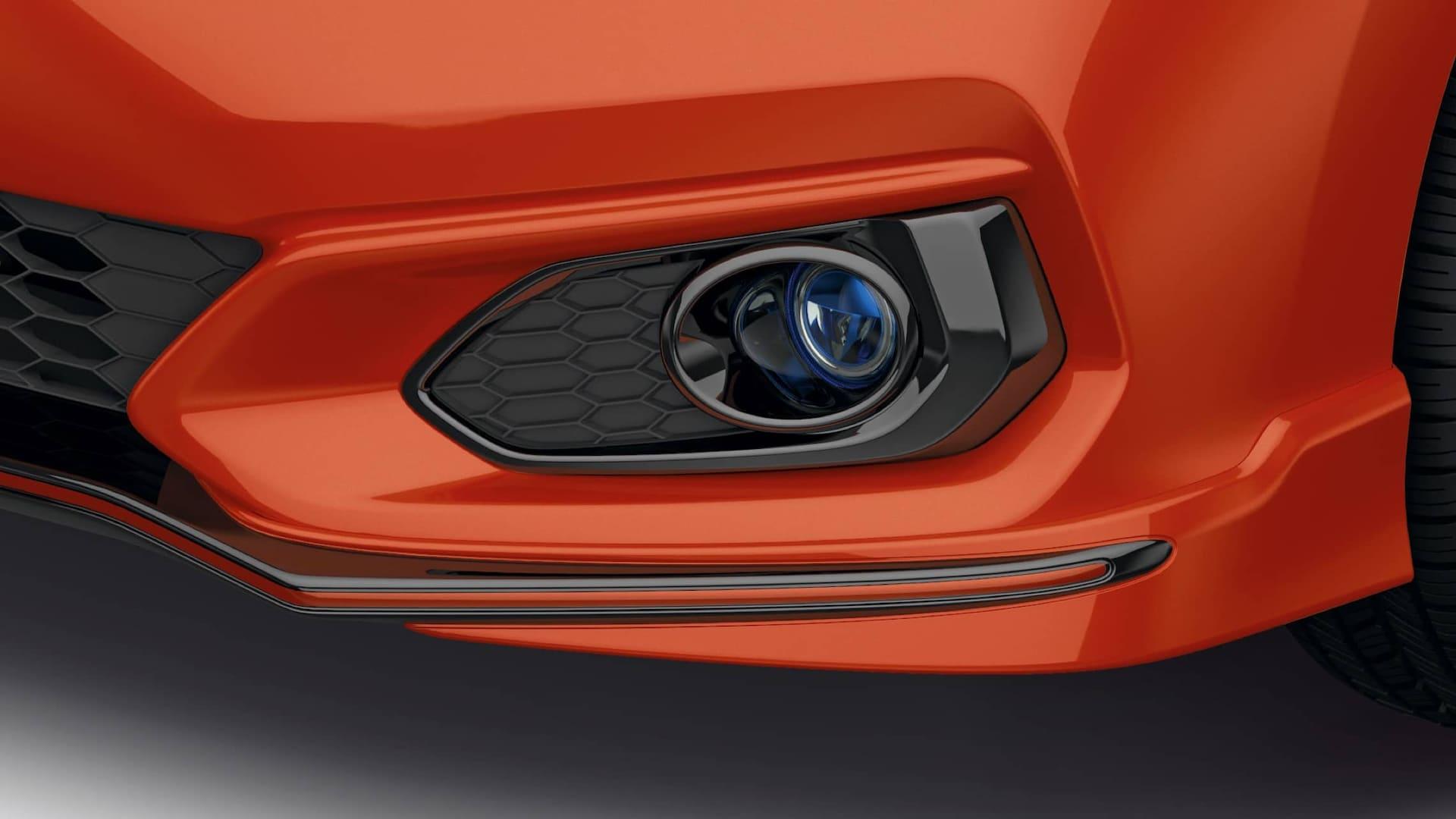 Vista frontal de 3/4 desde el lado del conductor del detalle de los faros antiniebla de LED del Honda Fit2019 en Orange Fury.