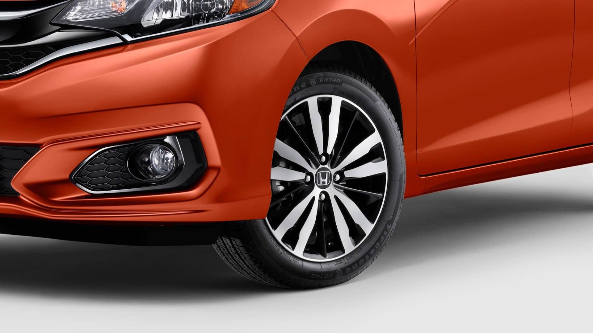 Vista de 3/4 desde el lado del conductor del detalle de la rueda de aleación de 16pulgadas del Honda Fit EX-L2019 en Orange Fury.