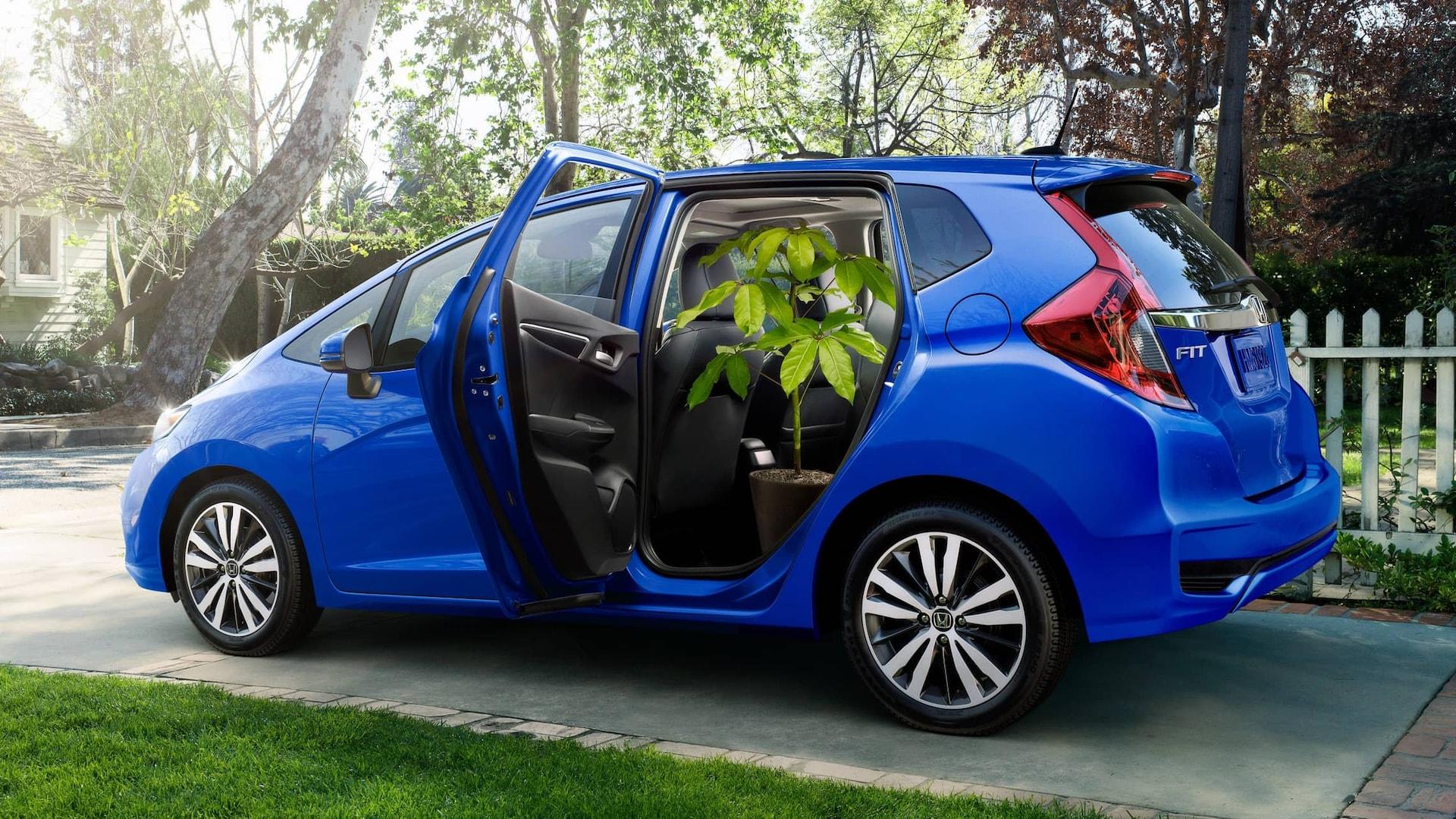 Vista trasera de7/8 desde el lado del pasajero del Honda Fit EX-L2019 en Aegean Blue Metallic con asientos Magic Seat® plegados en la segunda fila y accesorios originales de Honda.
