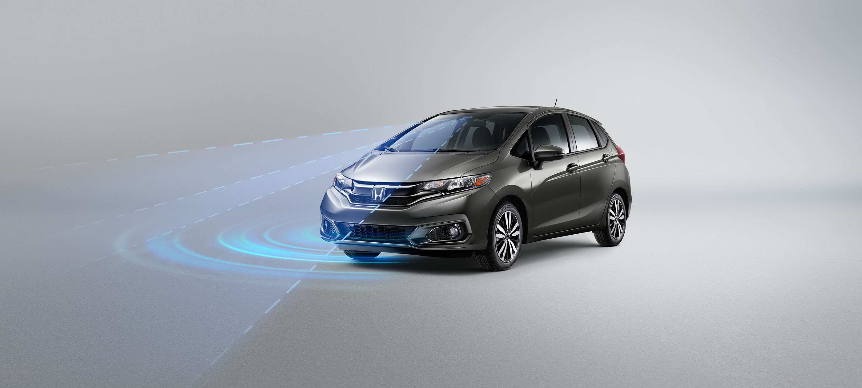 Front ¾ driver-side view of 2019 Honda Fit Sport CVT in Modern Steel Metallic with Honda Sensing® illustrated demonstration.