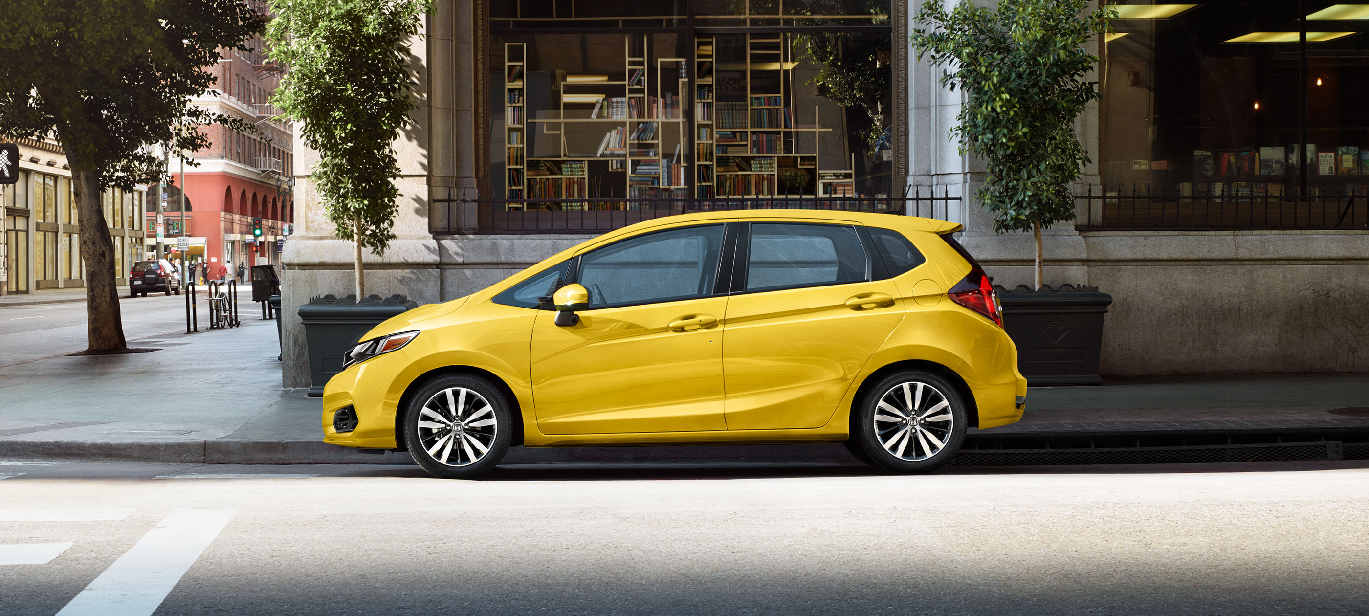 Driver-side profile view of 2019 Honda Fit Sport CVT in Helios Yellow Pearl parked on city street.