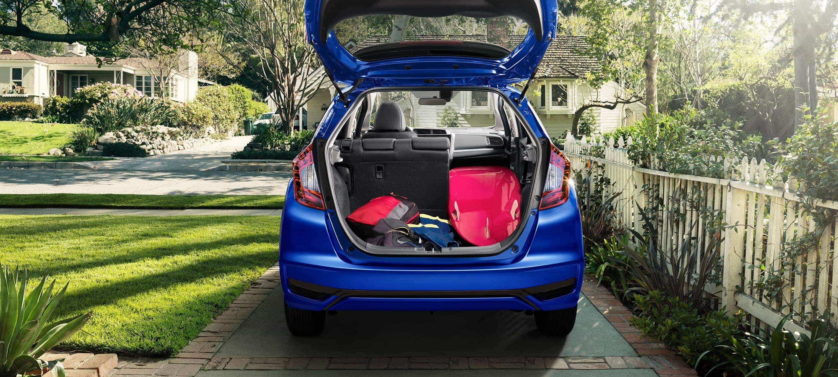 Rear view of 2019 Honda Fit Sport CVT in Aegean Blue Metallic with open trunk displaying cargo volume.