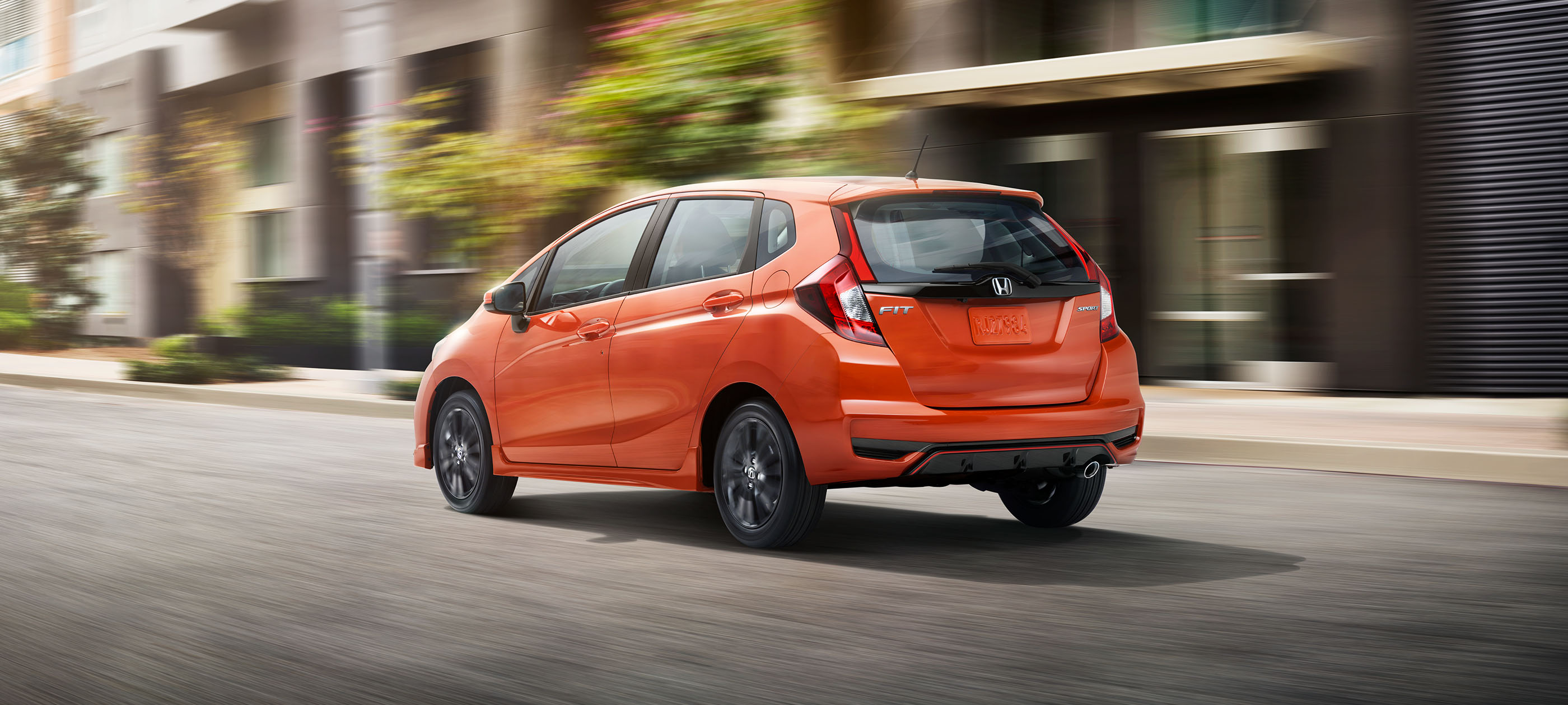 Rear ¾ driver-side view of 2019 Honda Fit Sport CVT in Orange Fury driving on city road.