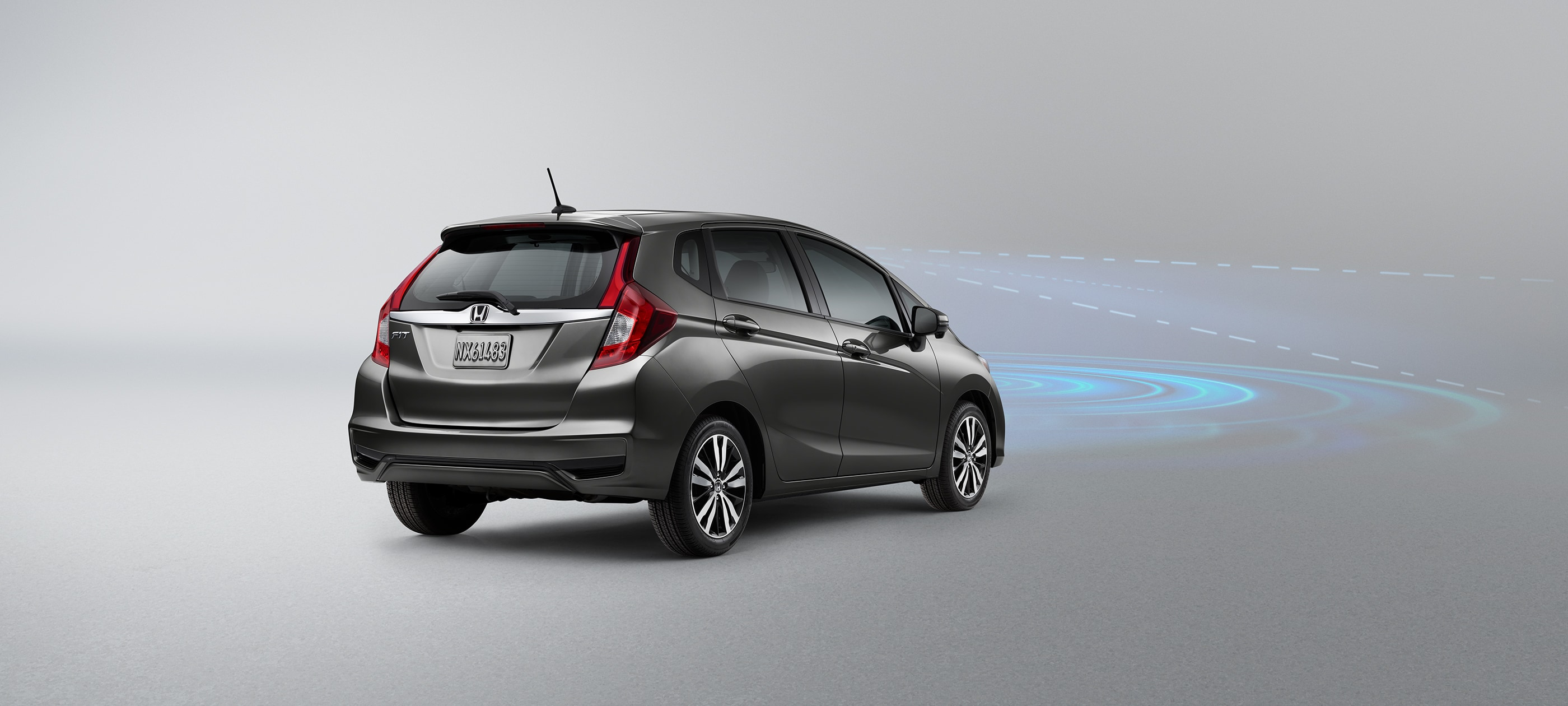 Rear ¾ driver-side view of 2019 Honda Fit Sport CVT in Modern Steel Metallic with Honda Sensing® illustrated demonstration.