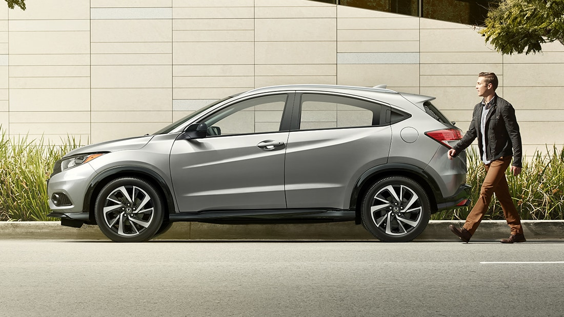 Driver's side view of the 2019 Honda HR-V Sport in Lunar Silver Metallic parked outside of modern building.