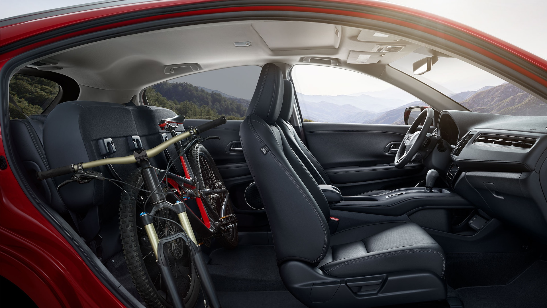 Interior passenger's side view of the 2019 Honda HR-V Touring in Black Leather with folded rear seats stowing a bike.