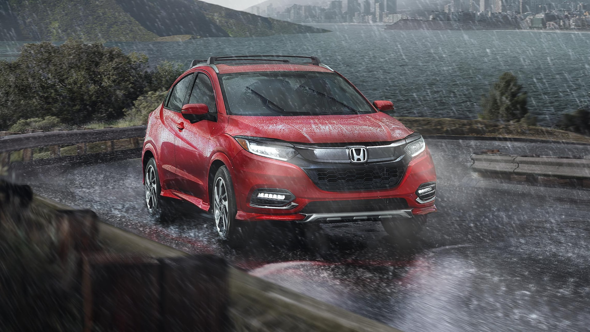Front 7/8 passenger's side view of the 2019 Honda HR-V Touring in Milano Red driving on lakeside road in the rain.