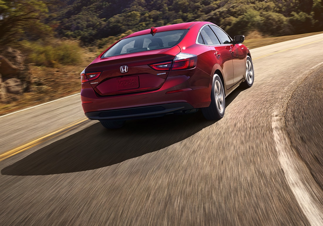 Rear passenger-side view of the 2020 Honda Insight EX in Crimson Pearl driving on winding mountain road.