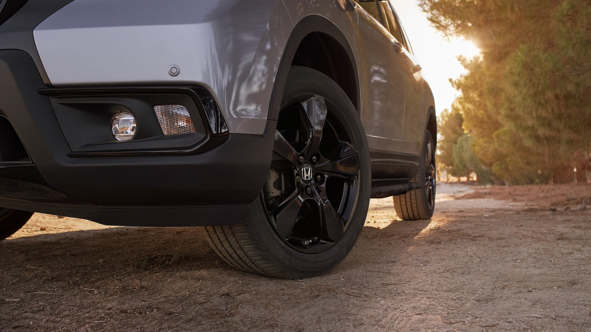 20-inch black alloy wheels on the 2019 Honda Passport Elite, in Lunar Silver Metallic with Honda Genuine Accessories, driving on a rugged road.