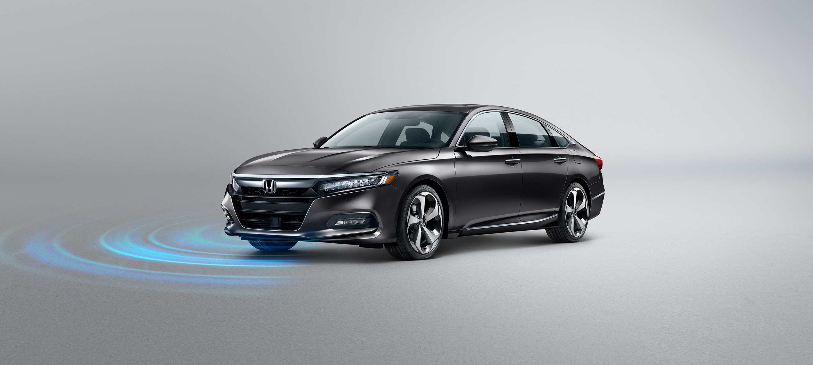 Front driver-side view of Honda Accord Touring 2.0T in Modern Steel Metallic with Honda Sensing® illustrated graphic.