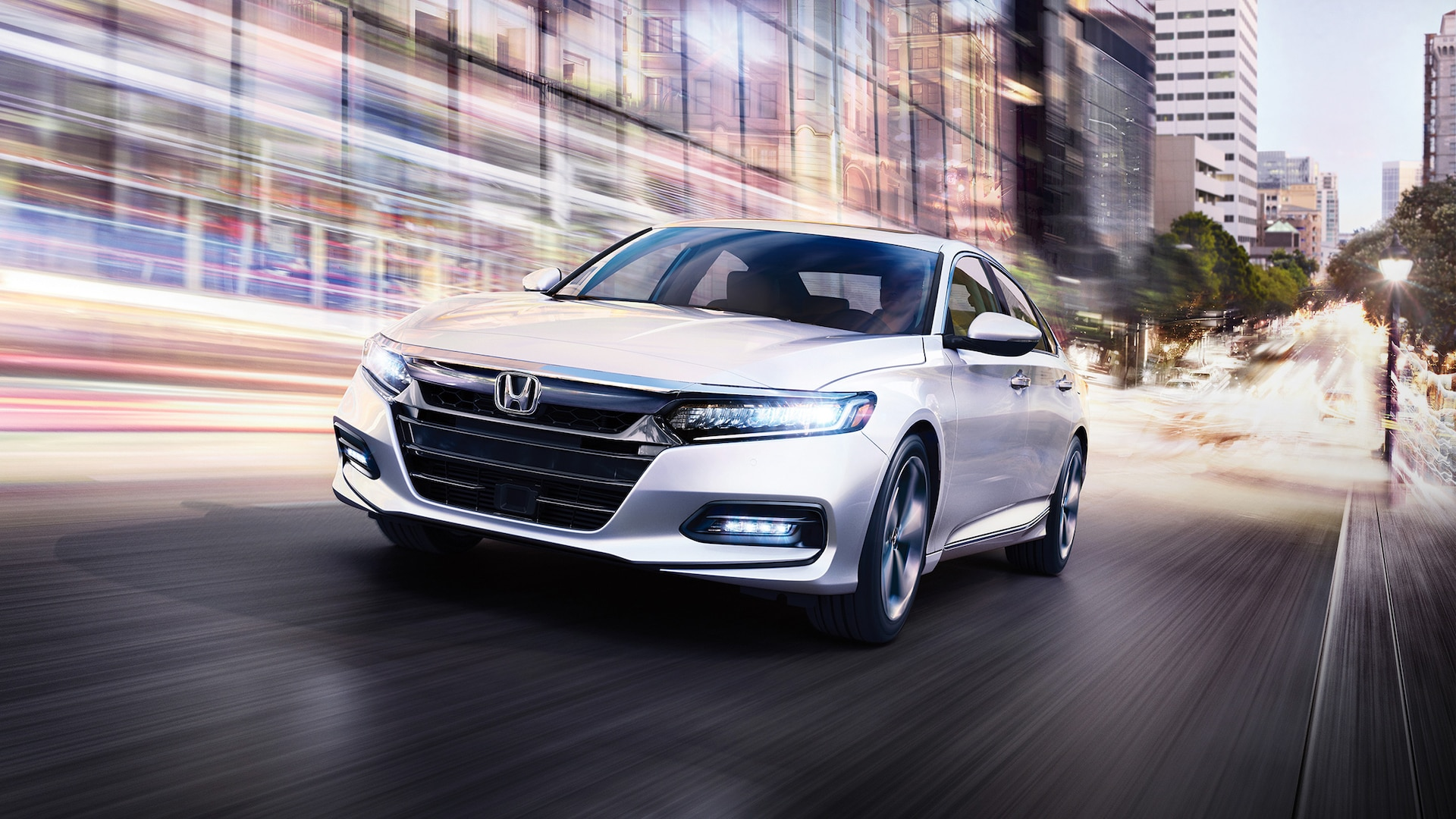 Front view of the 2020 Honda Accord Touring 2.0T in Platinum White Pearl, driving in city environment.