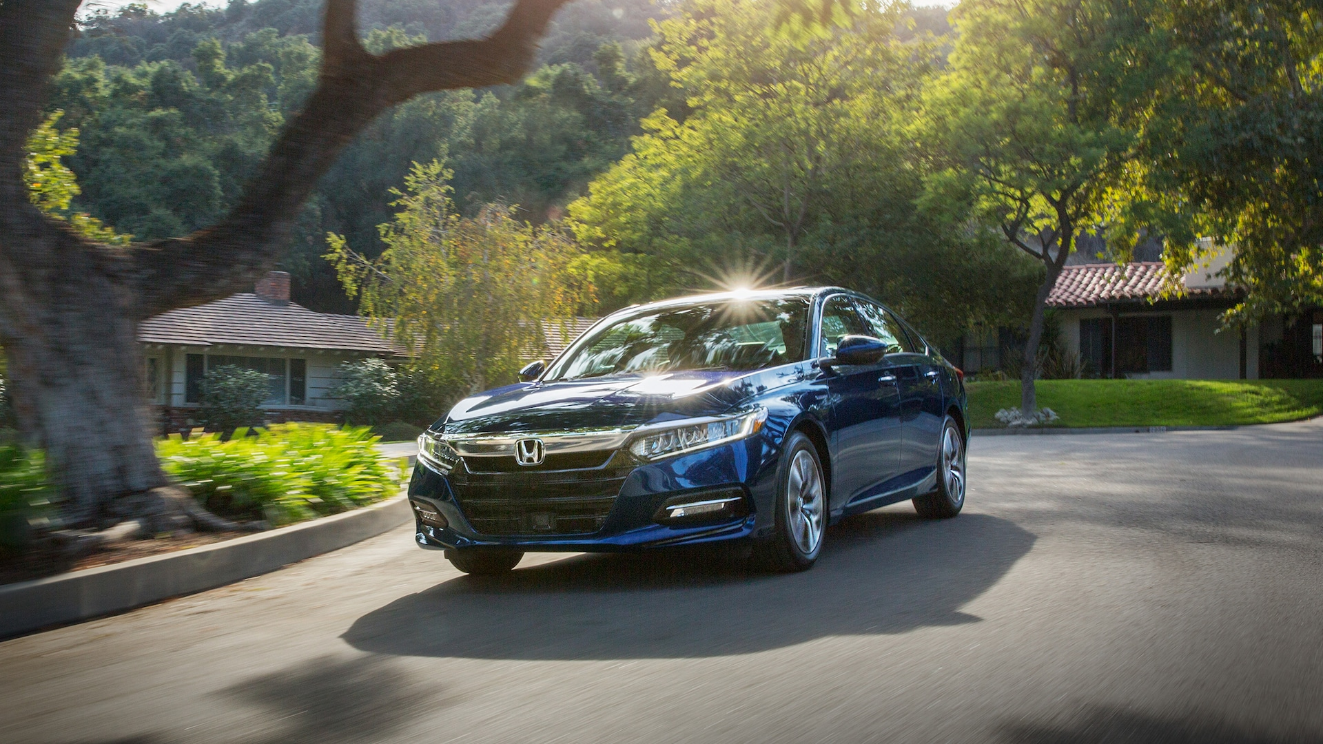 Front driver-side view of the 2020 Honda Accord Hybrid Touring in Obsidian Blue Pearl, driving through residential neighborhood.