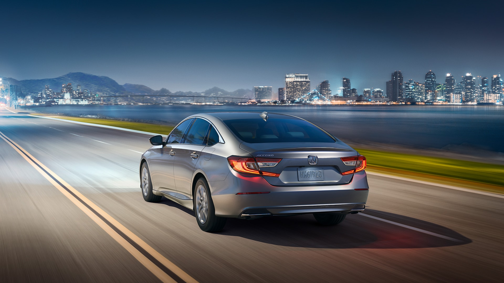 Rear driver-side view of the 2020 Honda Accord LX in Lunar Silver Metallic, driving at night using the auto high-beam headlights feature.