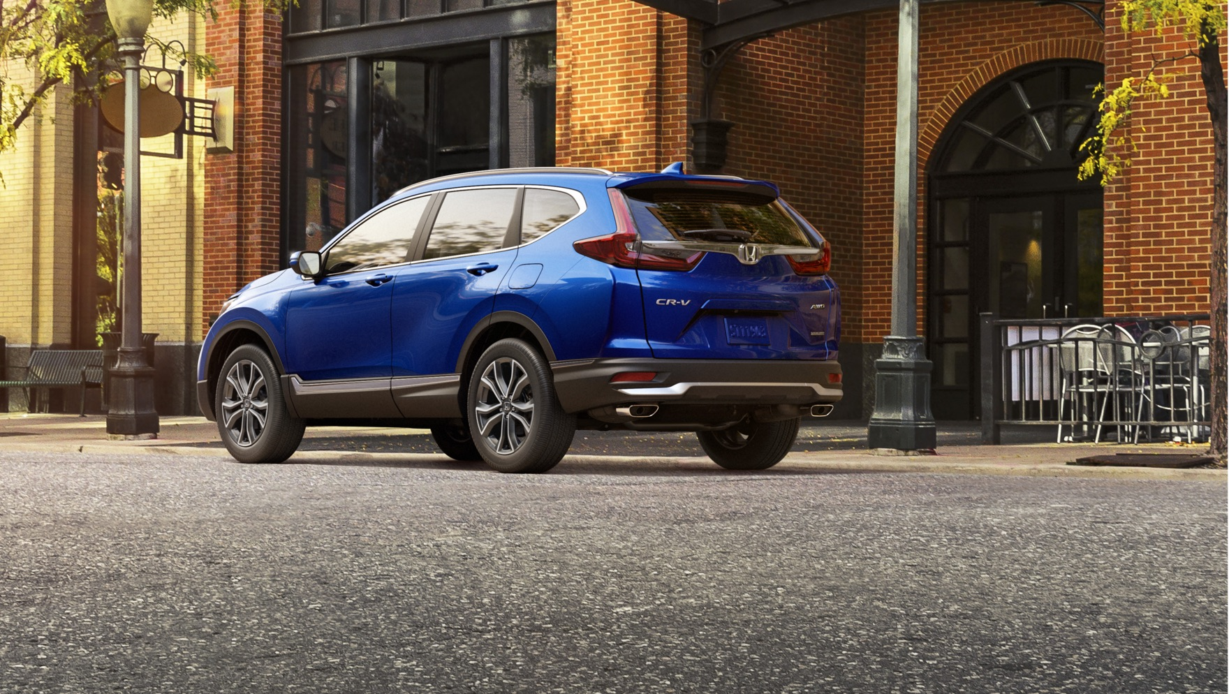 Rear driver-side view of the 2020 Honda CR-V in Aegean Blue Metallic parked on a city street.