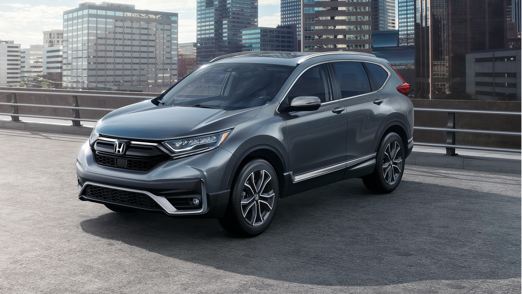 Front driver-side view of the 2020 Honda CR-V in Modern Steel Metallic against a city background.