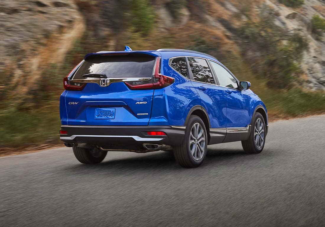 Rear-passenger three-quarter view of the 2020 Honda CR-V Touring in Aegean Blue Metallic driving on a mountain road.
