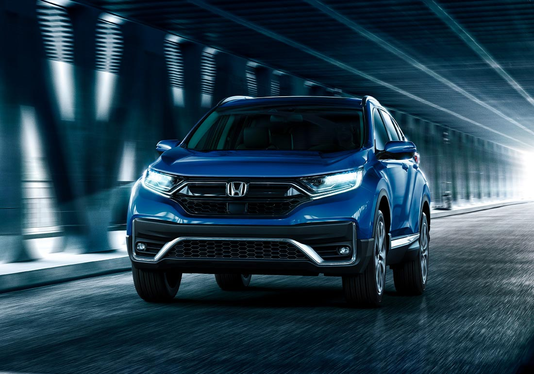Seven-eighth front driver-side view of the 2020 Honda CR-V AWD Touring in Aegean Blue Metallic, driving on a bridge in an urban environment.