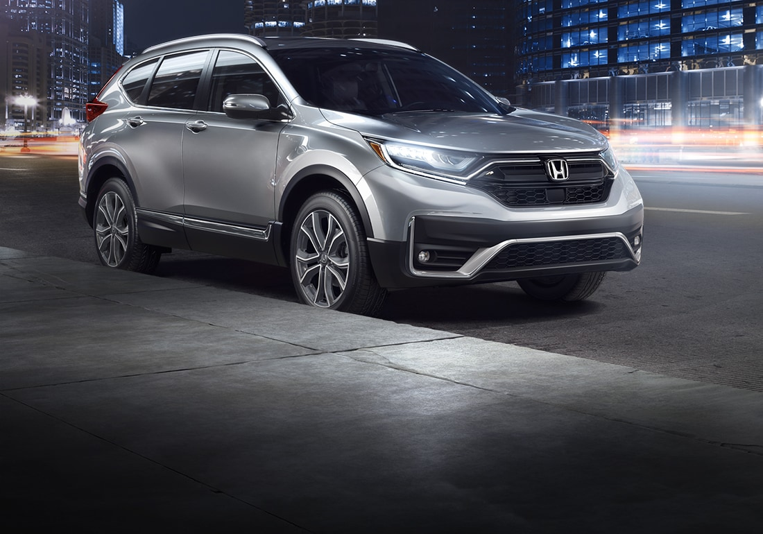 Front-passenger view of the 2020 Honda CR-V in Lunar Silver Metallic on a city street at night.