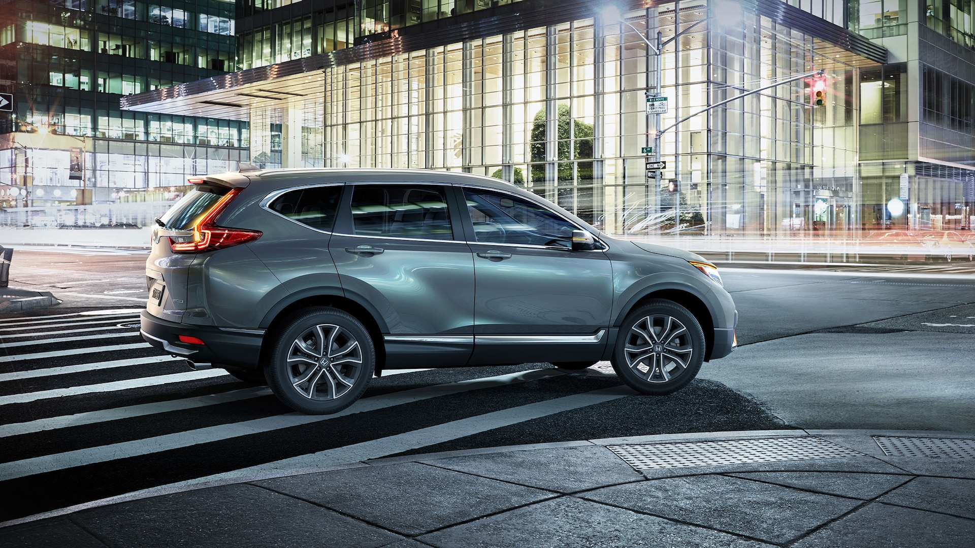 Passenger-side profile view of the 2020 Honda CR-V Touring in Sonic Gray Pearl, driving in an urban environment at night.