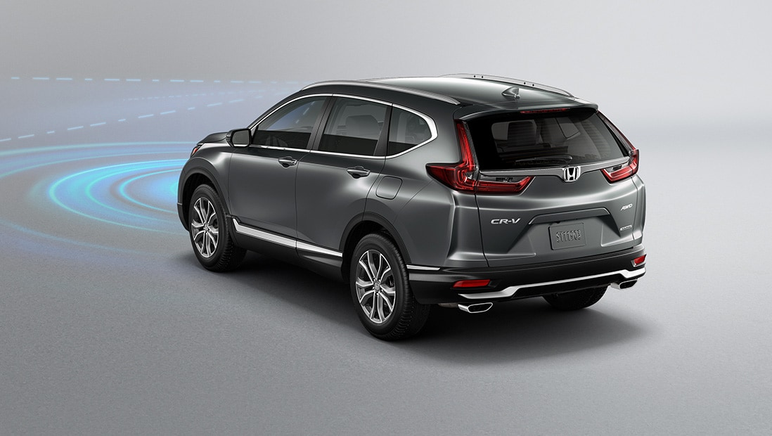 Rear 3/4 driver-side view of 2020 Honda CR-V Touring in Modern Steel Metallic demonstrating Honda Sensing®.