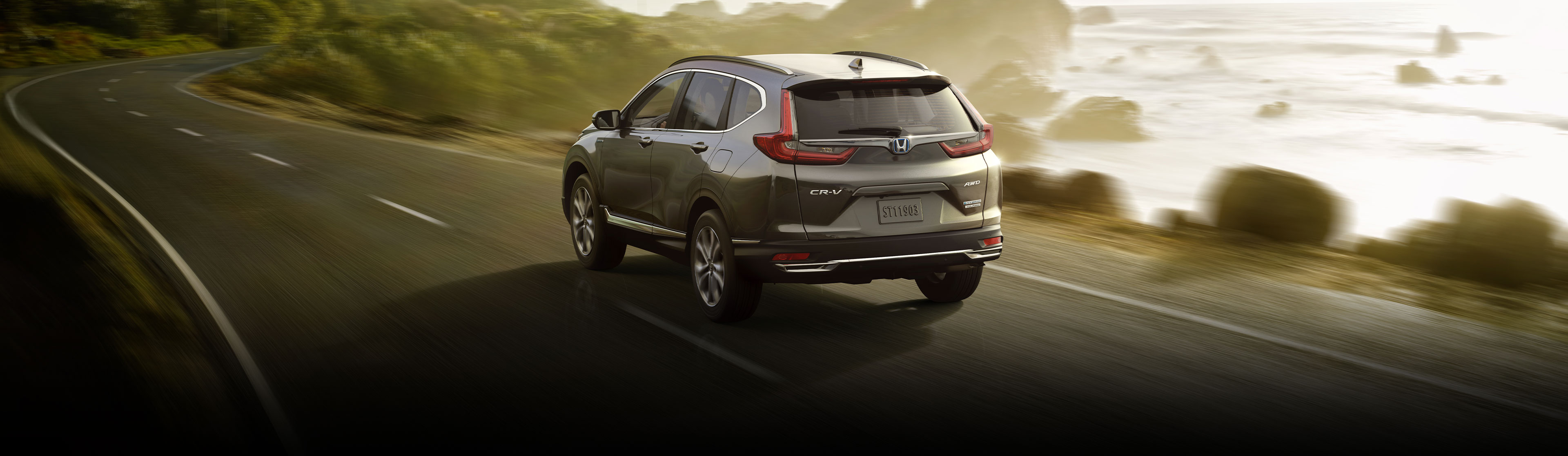 Rear driver-side view of the 2020 CR-V Hybrid Touring in Modern Steel Metallic, driving along a coastal highway.