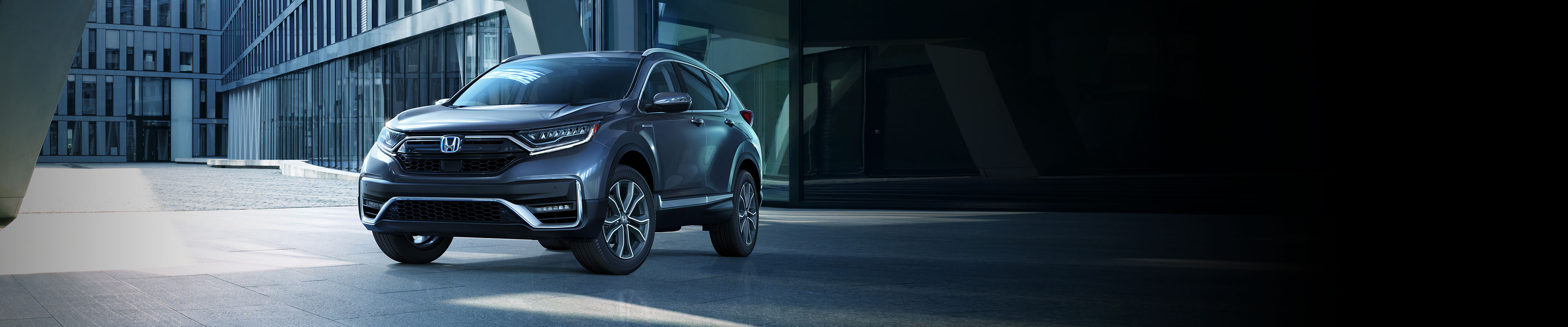Front driver-side view of the 2020 CR-V Hybrid Touring in Modern Steel Metallic, parked in front of modern office building.