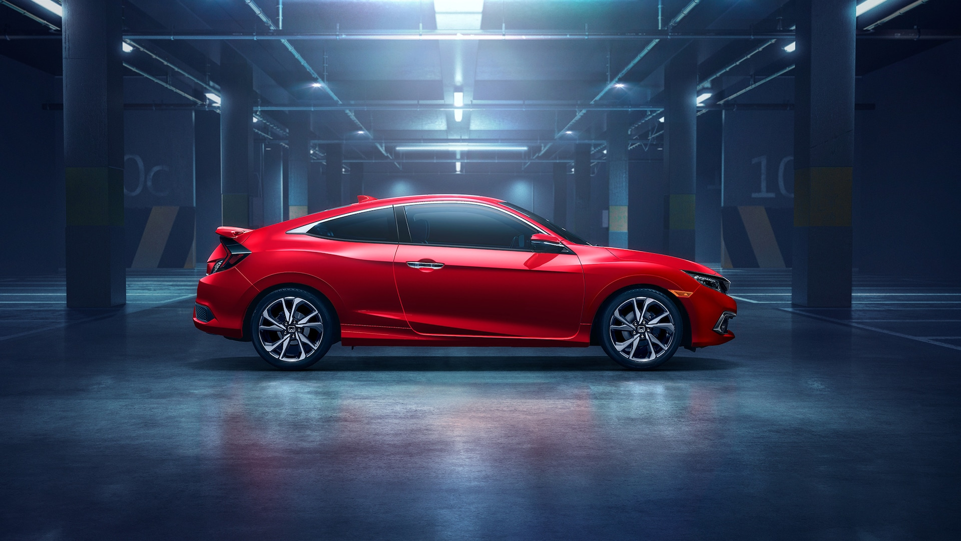Passenger-side view of the 2020 Honda Civic Touring Coupe in Rallye Red, parked in a garage.