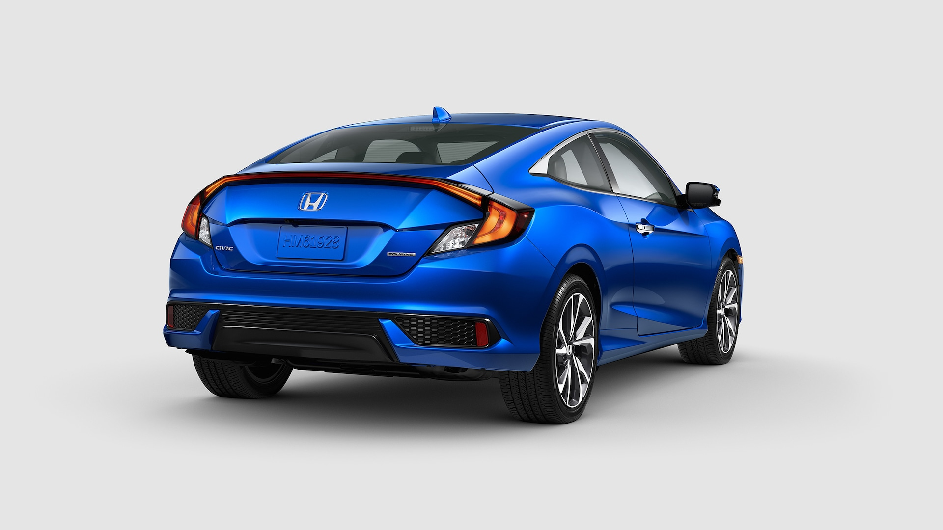 Rear passenger-side view of the the 2020 Honda Civic Touring Coupe in Aegean Blue Metallic displaying taillights with LED light bars.