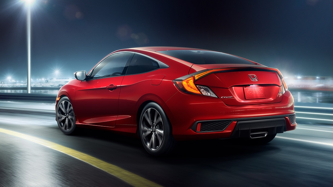 Rear driver-side view of the 2020 Honda Civic Sport Coupe in Rallye Red, driving on a highway.