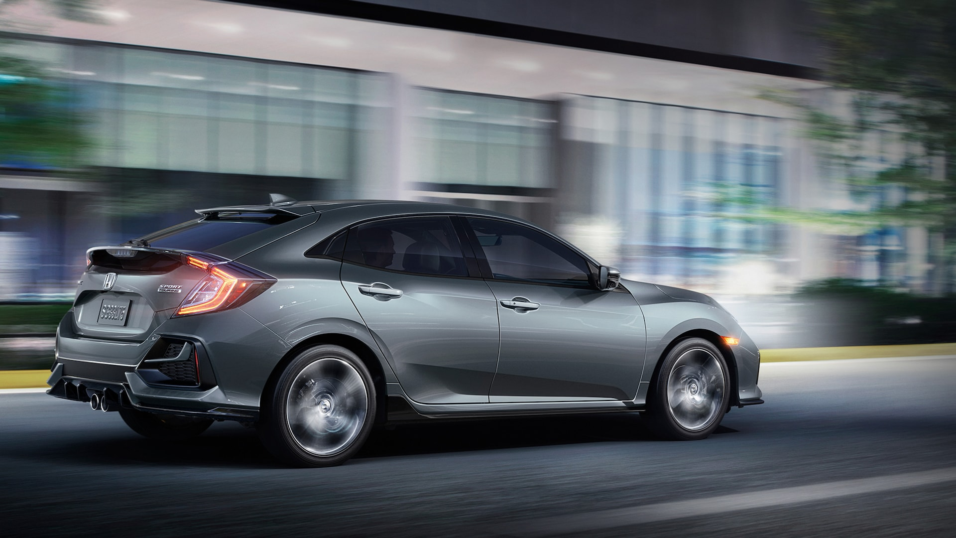 Rear driver-side 7/8 view of 2020 Honda Civic Sport Touring Hatchback in Sonic Gray Pearl.