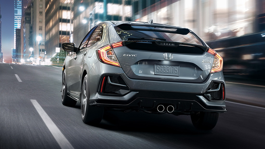 Rear 7/8 driver-side view of 2020 Honda Civic Sport Touring Hatchback, in Sonic Gray Pearl, driving on city road at night.