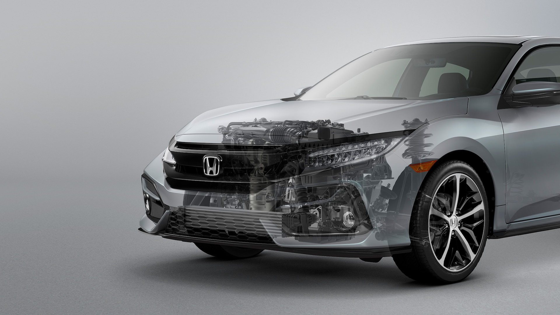 Front driver-side 3/4 view of 2020 Honda Civic Sport Touring Hatchback in Sonic Gray Pearl with engine cutaway illustration.