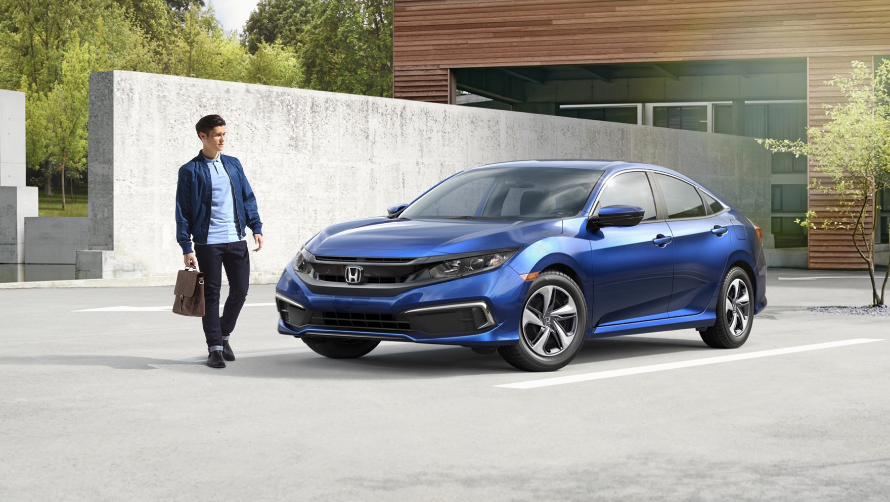 Front driver-side view of the 2020 Honda Civic LX Sedan in Aegean Blue Metallic parked in front of modern building.