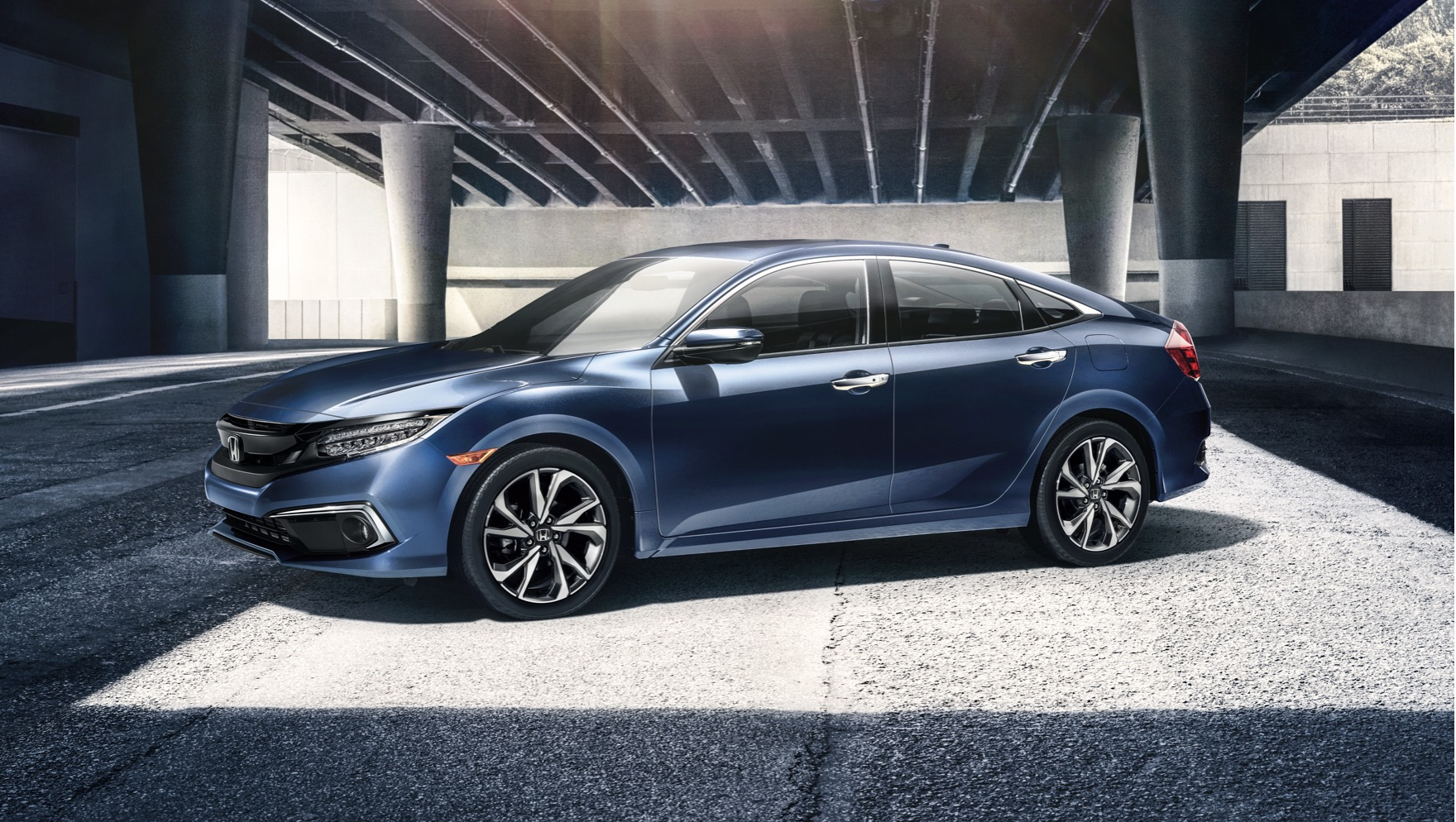Front driver-side view of the 2020 Honda Civic Touring Sedan in Cosmic Blue Metallic parked in front of modern building.