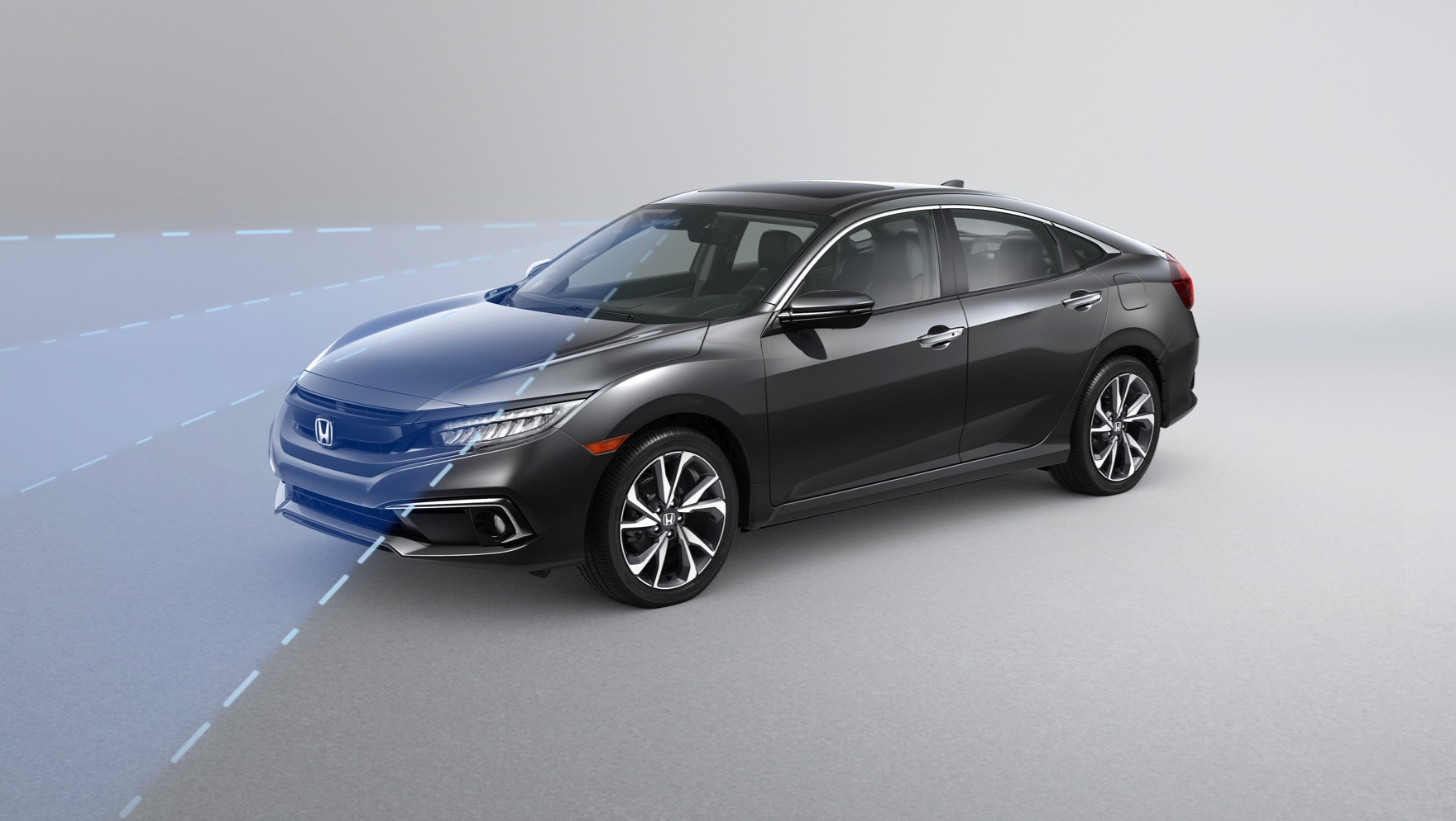 Front driver-side view of the 2020 Honda Civic Touring Sedan in Modern Steel Metallic with illustrated graphics demonstrating Honda Sensing® Road Departure Mitigation System feature.