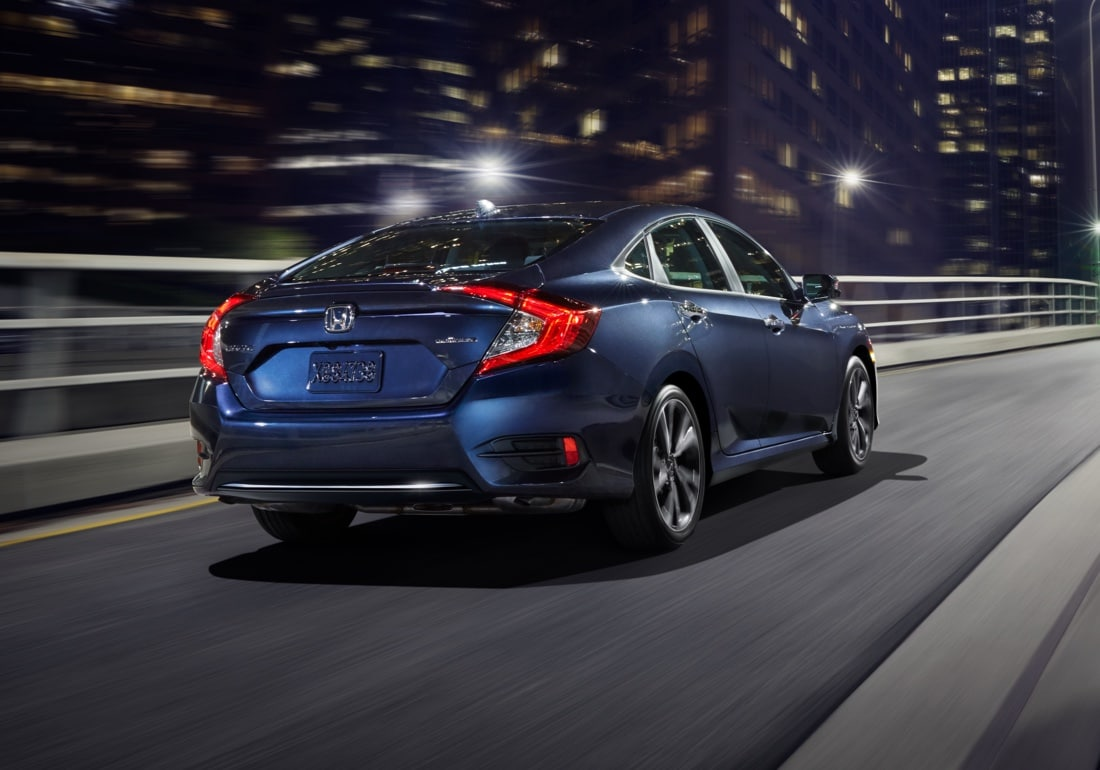 Rear passenger-side three-quarter view of the 2020 Honda Civic Touring Sedan in Cosmic Blue Metallic driving over a bridge at night.