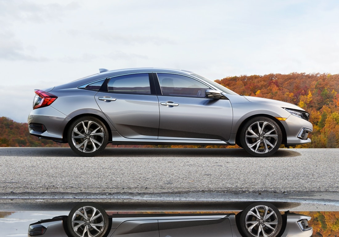 Passenger-side profile view of the 2020 Honda Civic Touring Sedan in Lunar Silver Metallic shown on a rural round in front of autumnal trees.